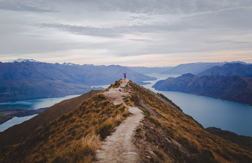 panoramic view of the roys peak in new zealand with low mountains in the distance under cloudscape